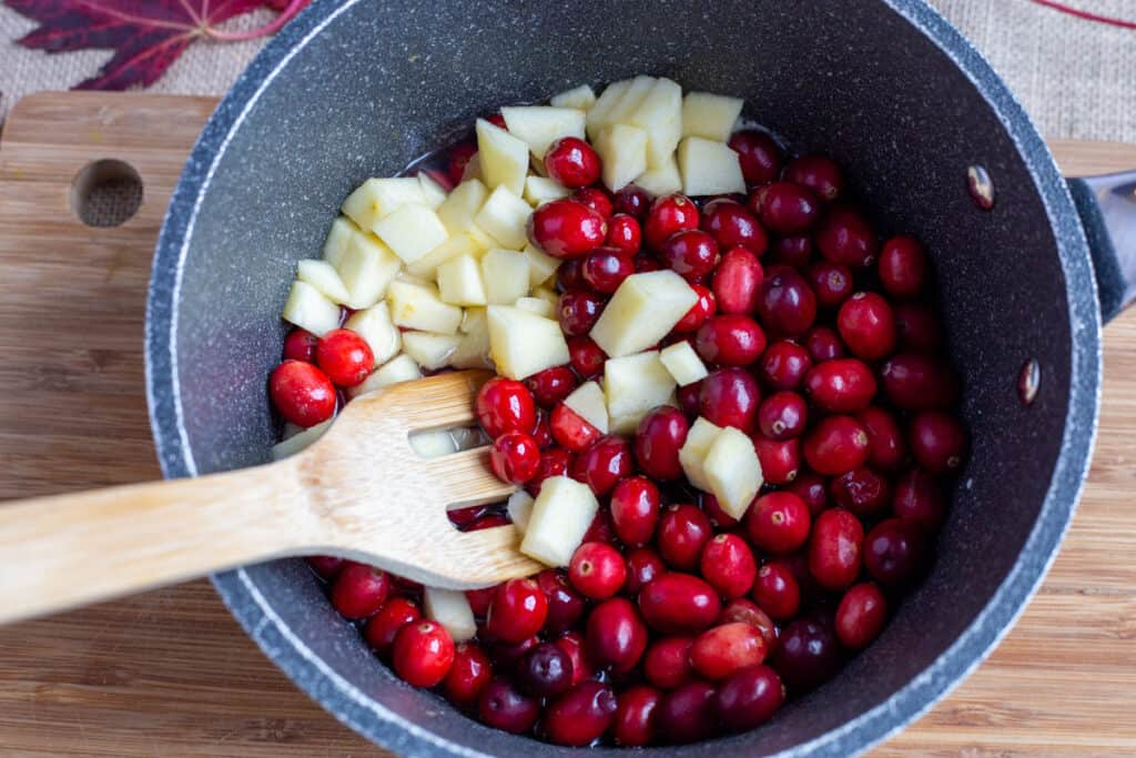 Cranberries, apples, water and sugar in a saucepan with a wooden spoon. The pot is sitting on a wooden cutting board.