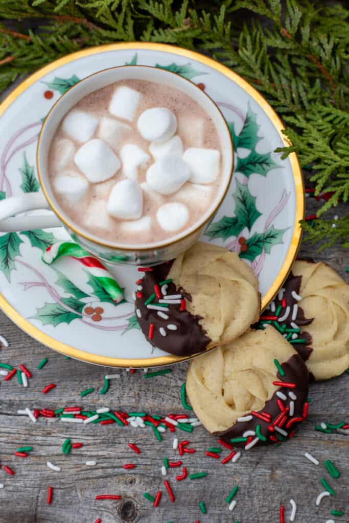 Three chocolate-dipped butter cookies lean against a Christmas tea cup and saucer that is filled with hot chocolate.