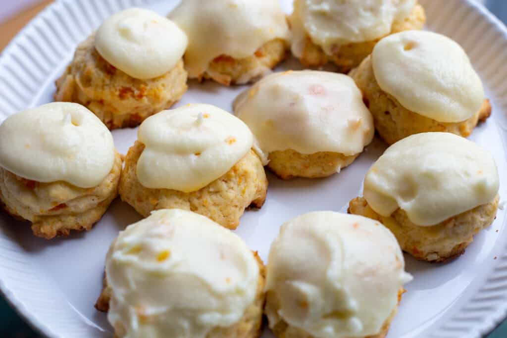 Ten carrot cookies with orange icing sit on a white pate.