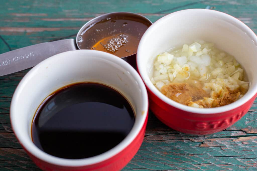 Ingredients for honey garlic marinade are in small red glass dishes and a measuring cup.