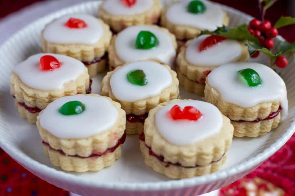 A tray of Empire cookies with a sprig of holly for garnish.