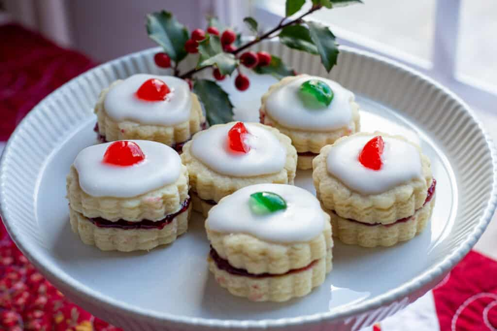 Five Empire Cookies sit on a footed white plate with a sprig of holly in the background for garnish.