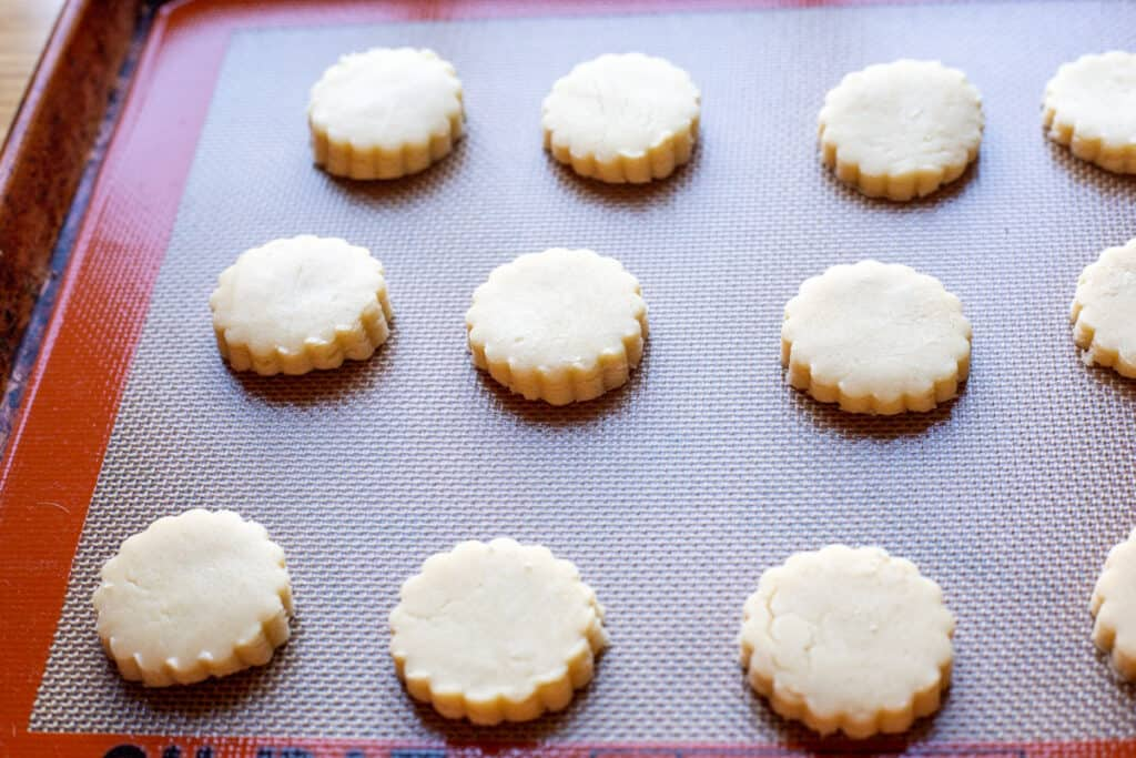 Twelve cut out round of cookie dough sit on a cookie sheet ready to to into the oven for baking.