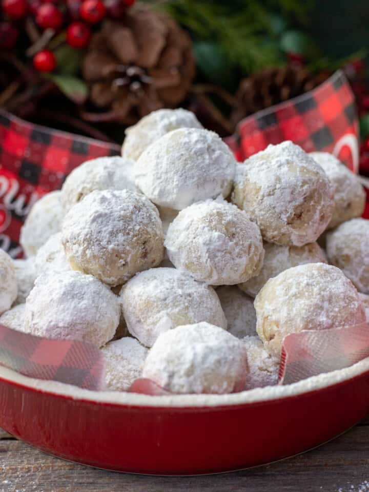 Snowball Cookies in red dish with black and red checked napkin.