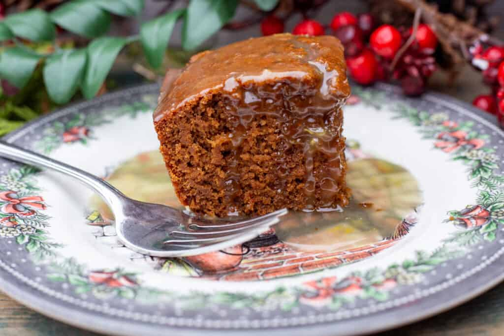 A piece of Gingerbread Squares with Lemon Sauce sits on a holiday plate with a fork to the side. There are red berries and greenery in the background.