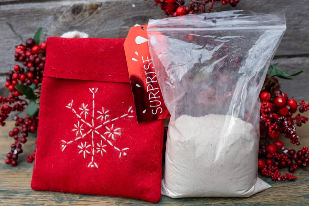 A plastic bag filled with Gingerbread Squares Mix. A red gift bag sits to the left of the plastic bag. Red berries and greenery featured for display purposes only in the background.