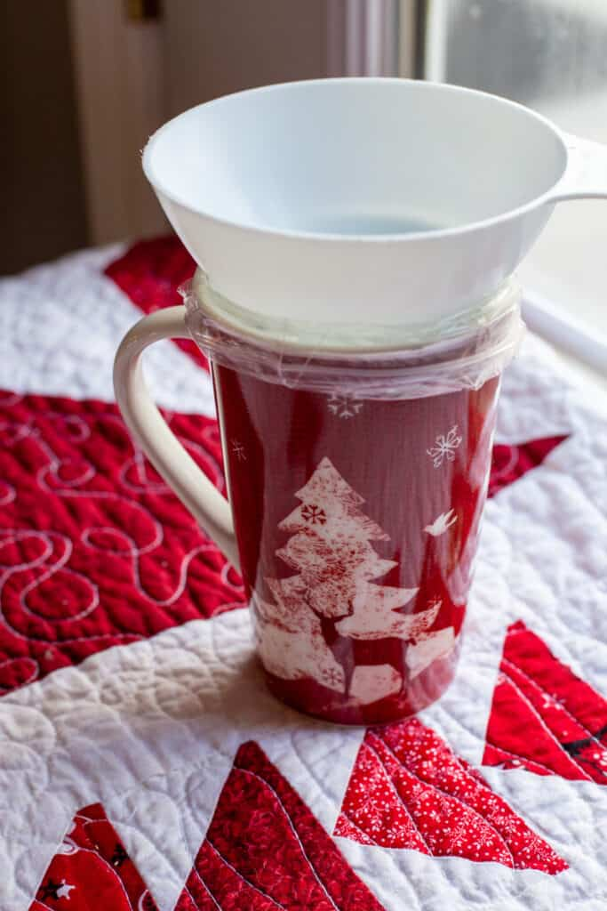 A glass mug with a plastic bag inside of it and a wide-mouth funnel sitting on top of the cup. This photo is showing the user how to easily put the Gingerbread Squares Mix into the bag without spilling the contents.