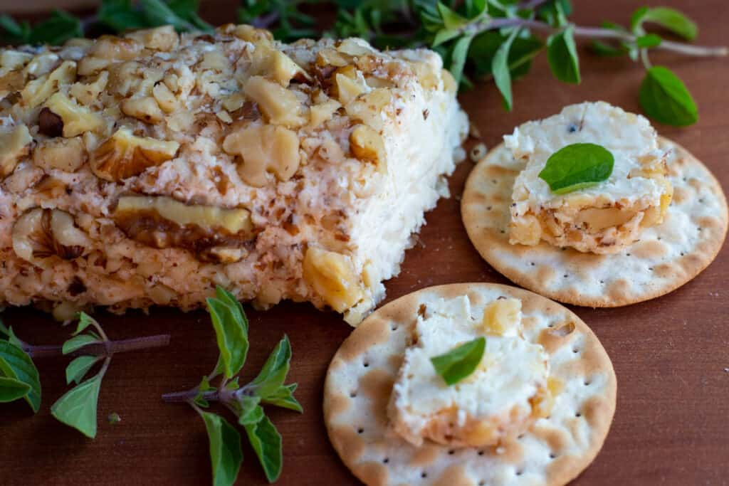 Smoked Gouda spread on a wooden board surrounded by chopped fresh herbs. Two crackers have a sampling of the gouda spread on top of them.