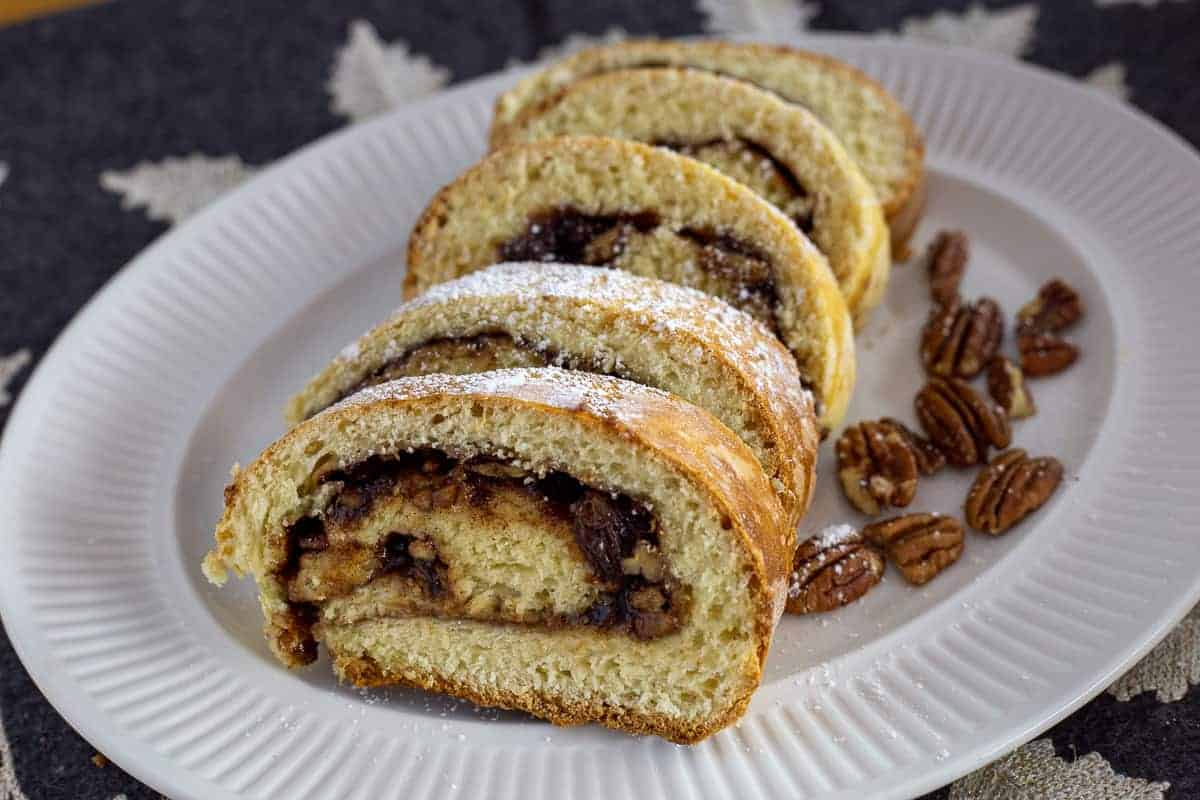 Five slices on cinnamon raisin swirl bread sitting on a white plate. Pecan are scattered around the plate for garnish.