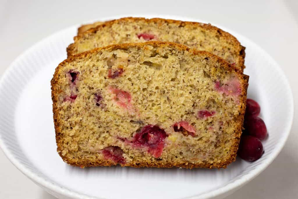 Slices of cranberry-banana bread on a white plate showing the texture of the bread.