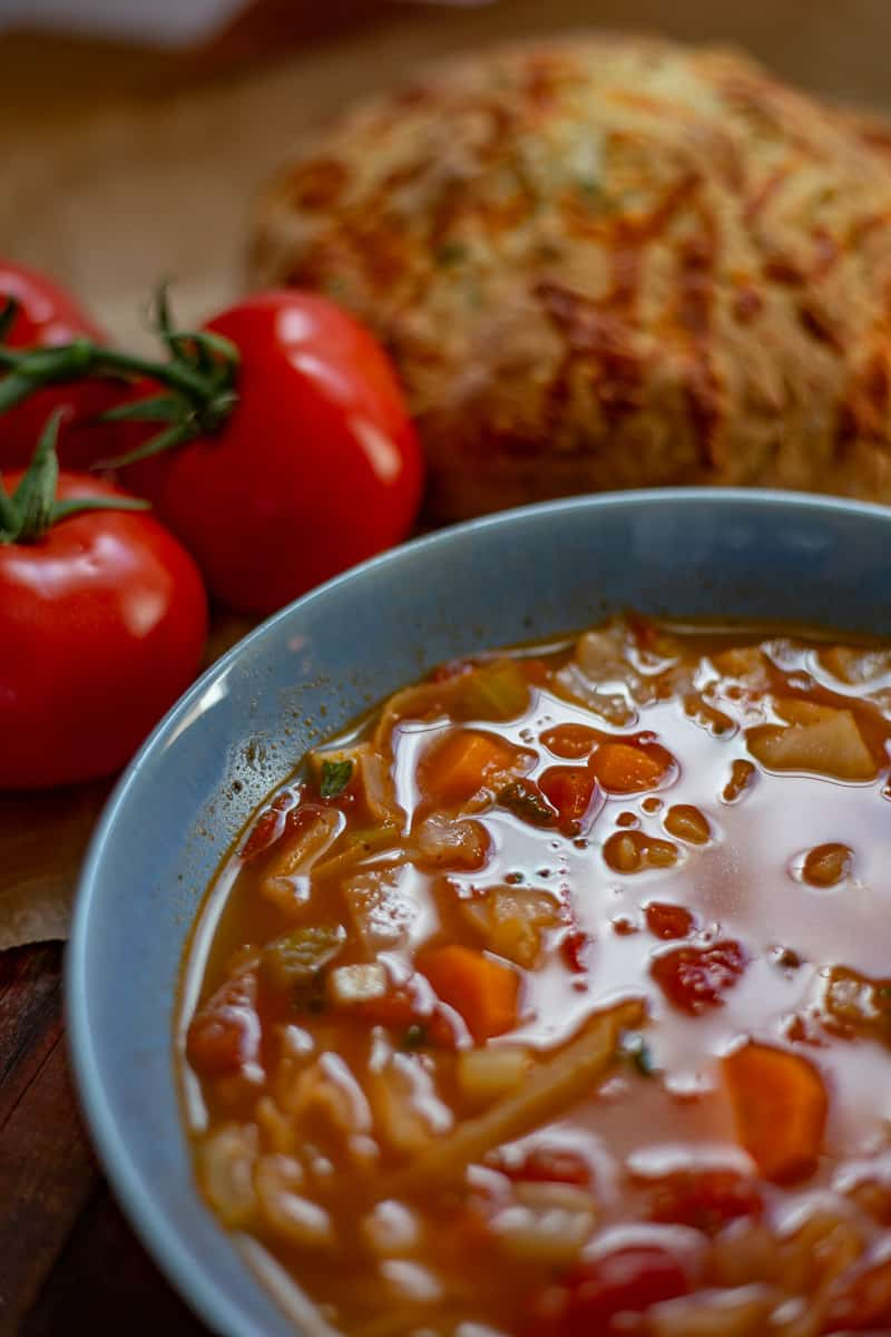Close up image of Hearty Vegetable Soup in blue bowl with vine tomatoes and bread in the background.