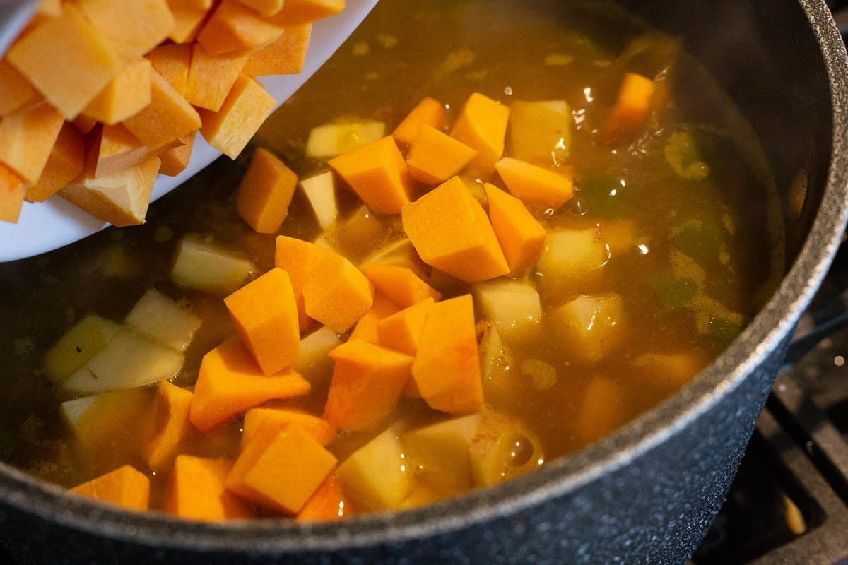 Butternut squash is cubed and added to the pot of soup.