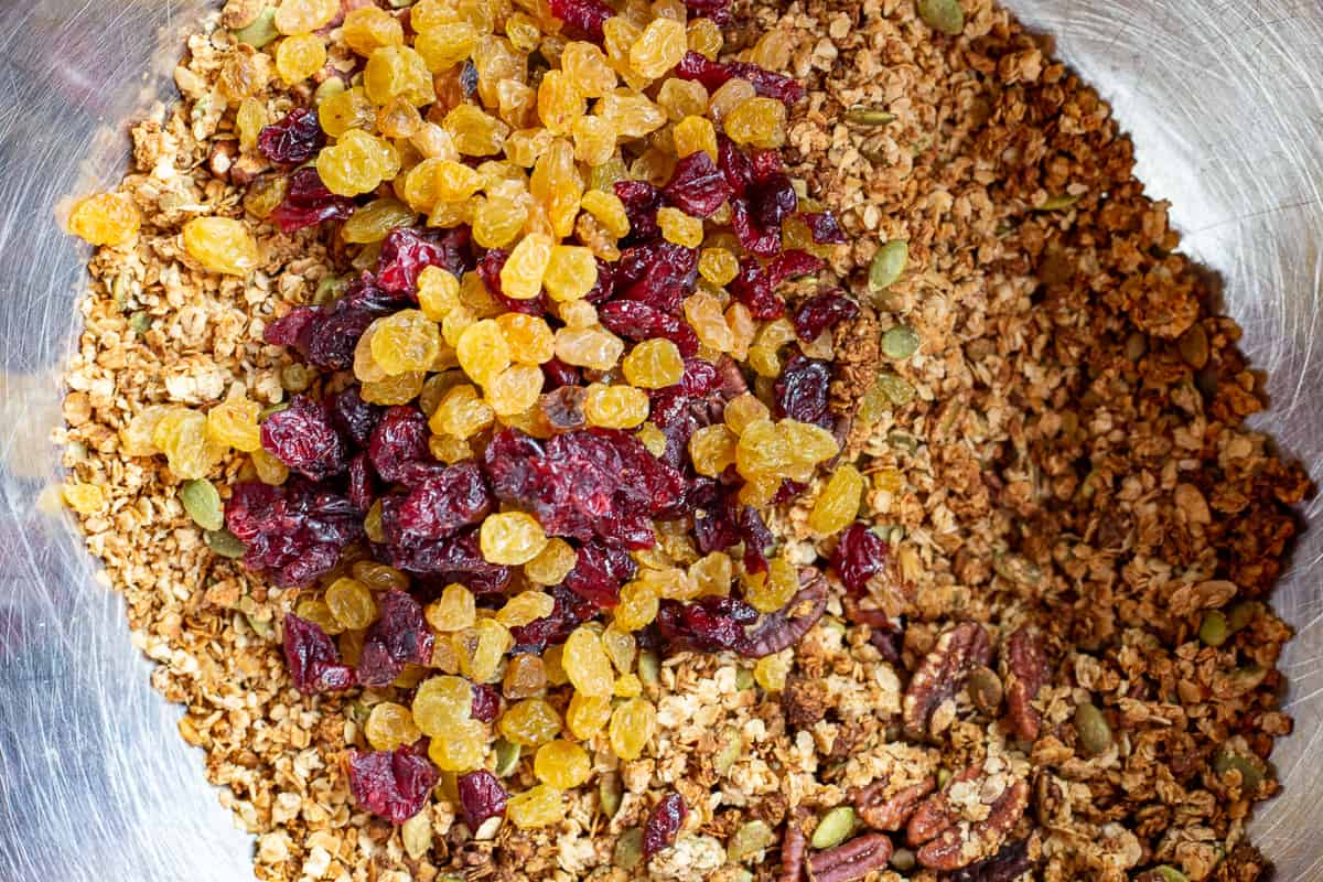 Baked granola in mixing bowl with golden raisins and cranberries.