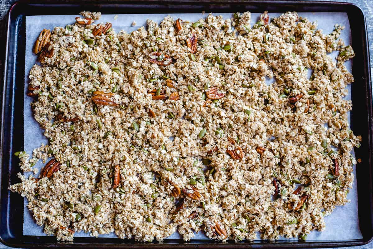 Rimmed baking sheet with granola ready to go into the oven.