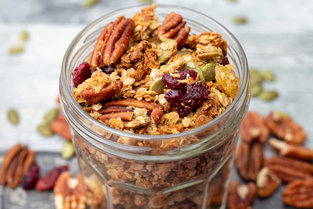 Granola in glass jar surrounded by scattered granola.