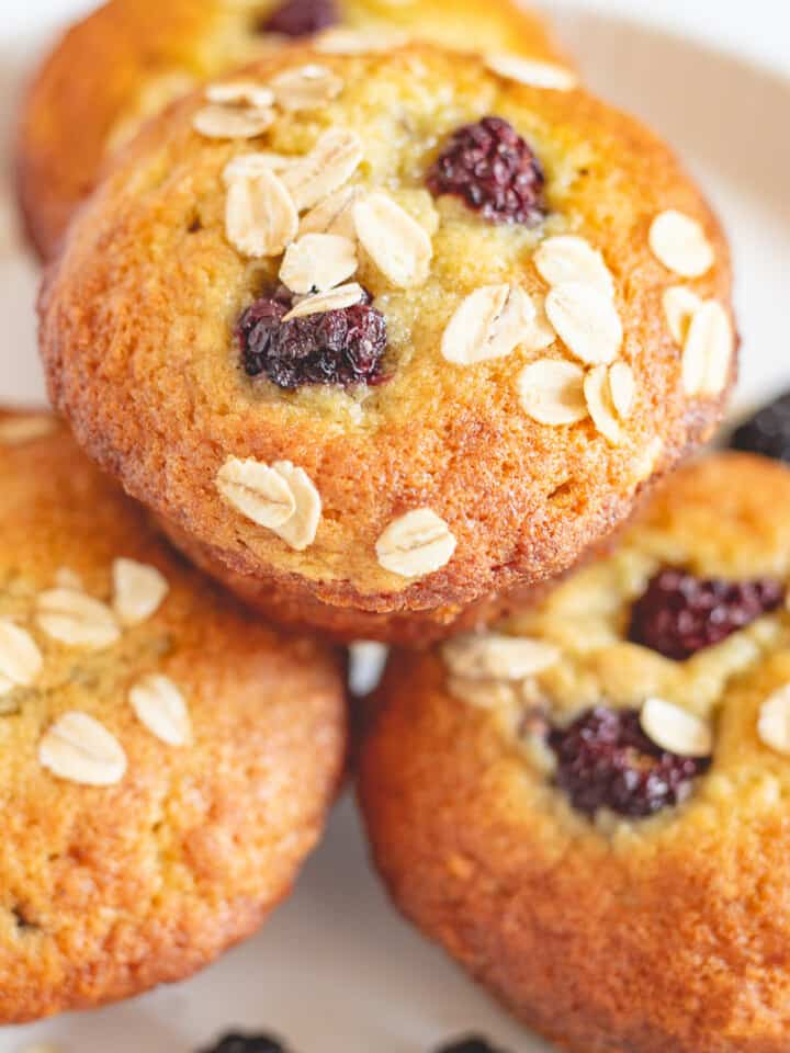 Close up image of Banana Blackberry Muffins on white plate.