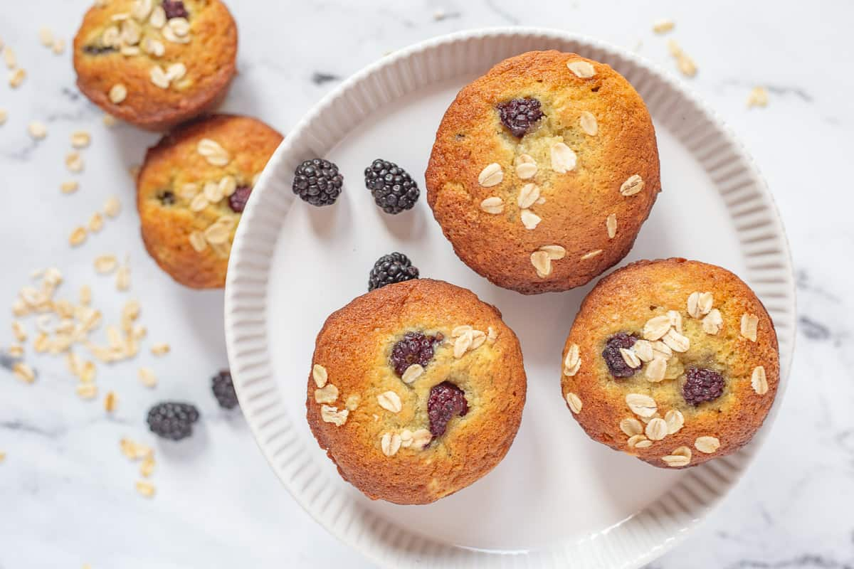 Overhead image of 5 muffins on white plate..