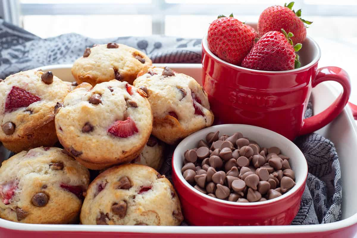 A dozen muffins in red dish with bowl of chocolate chips and strawberries beside it.