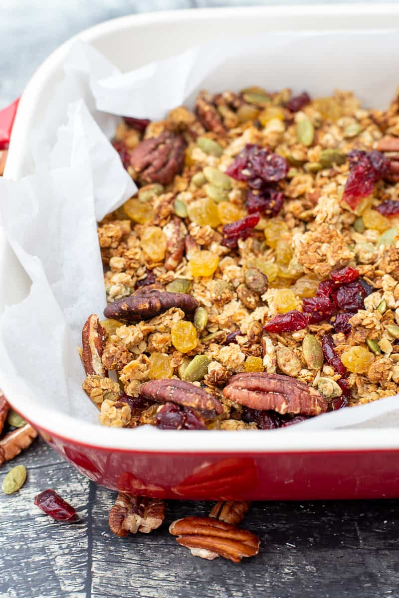 Close up image of Homemade Granola in red dish with parchment paper.