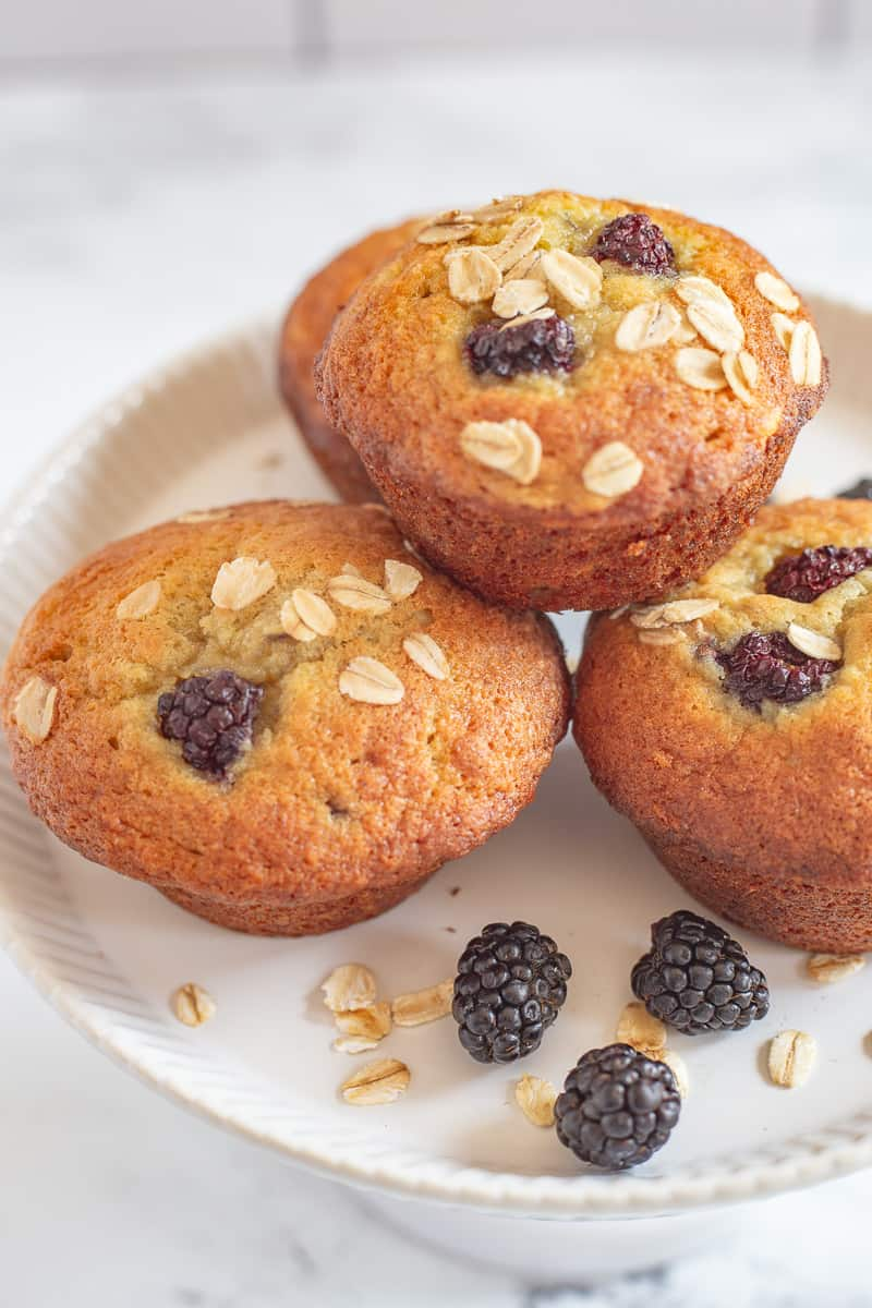 Side view of muffins on white footed plate.