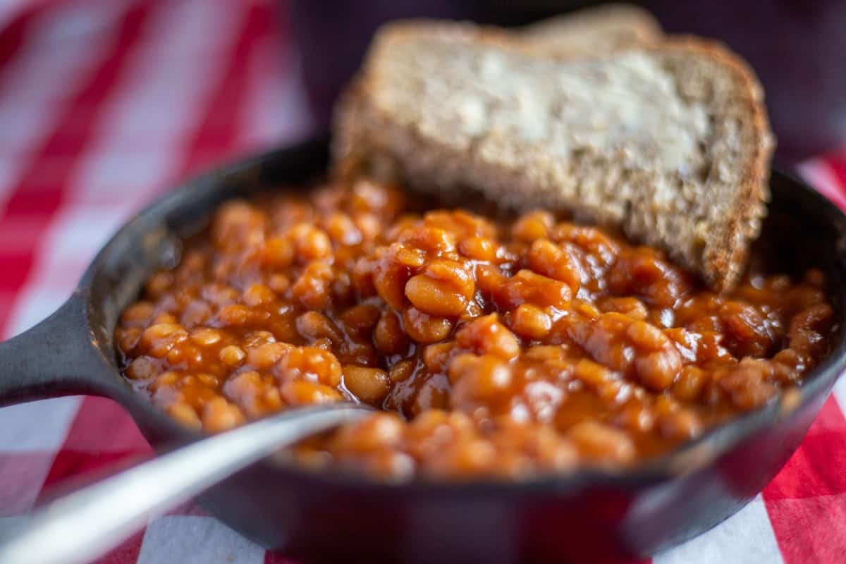 Close up image of baked beans in cash iron skillet with buttered bread and fork.