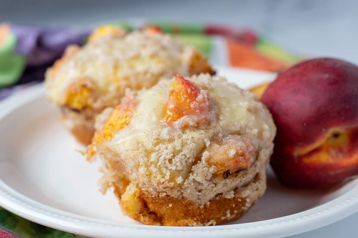 Easy peach muffins on white plate with peach in the background.