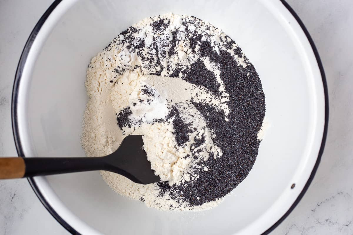 Dry ingredients and poppyseeds in mixing bowl with spoon.