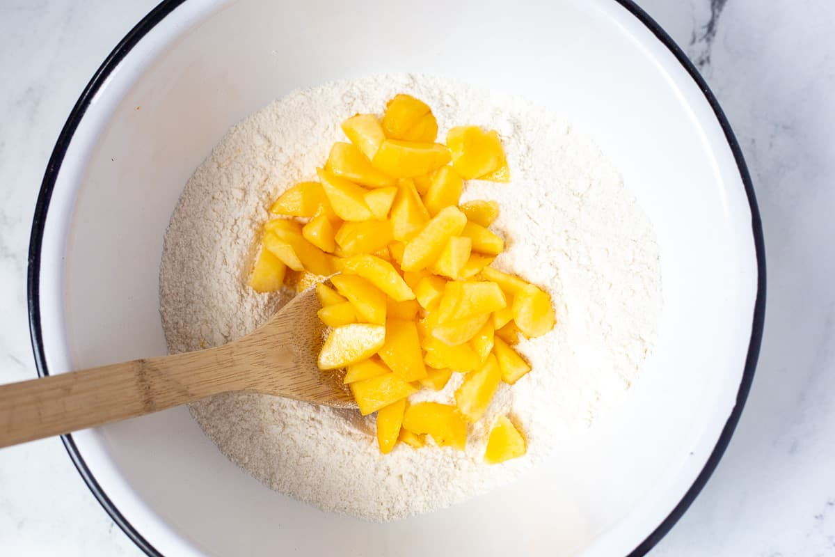 Chopped peaches are added to dry ingredients in mixing bowl.