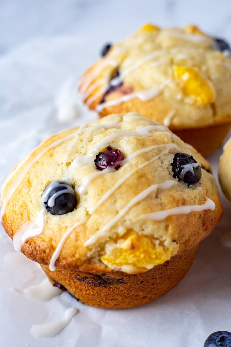 Close up image of Bakery Style Blueberry Peach Muffins.