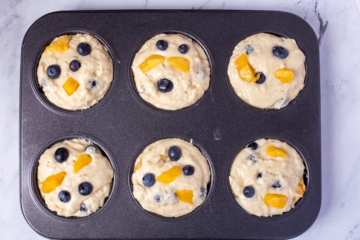 Muffin batter in muffin tins ready to go into the oven.