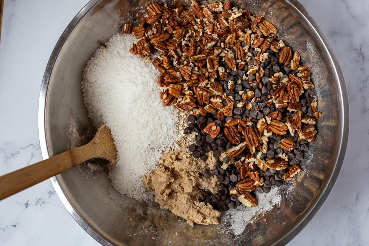 Pecans, chocolate chips and coconuts and rolled oats are added to cookie dough in mixing bowl.
