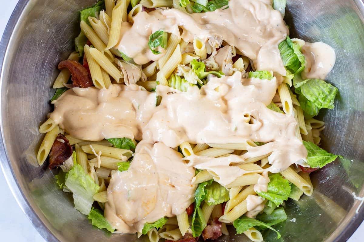 Salad dressing is poured over pasta salad ingredients.
