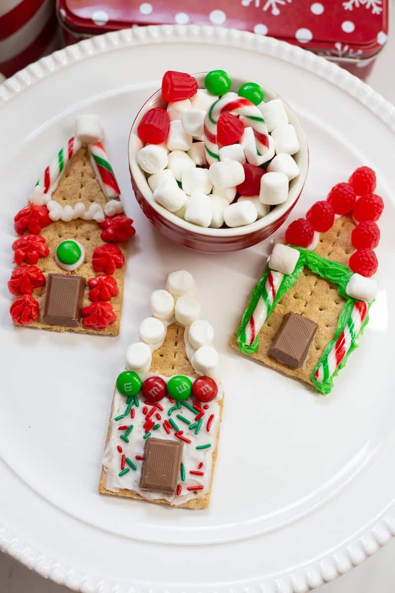 Three s'mores gingerbread cookies on white plate with small red bowl of candies.