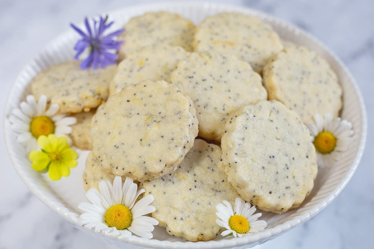 Lemon Poppy Seed Shortbread Cookies on a white plate with fresh wildflowers as garnish.
