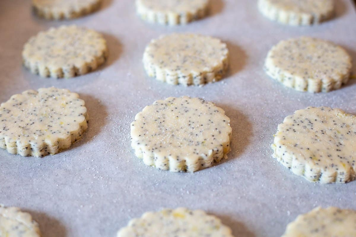 Cookies are cut out and sprinkled with granulated sugar on a parchment paper-lined baking sheet.