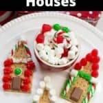 Close up image of three no-baked s'mores gingerbread houses on a white plate.