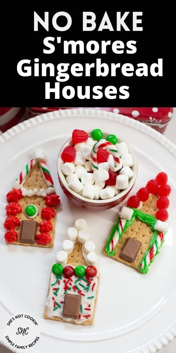 Three decorated s'mores gingerbread houses with a bowl of candies on a white plate.