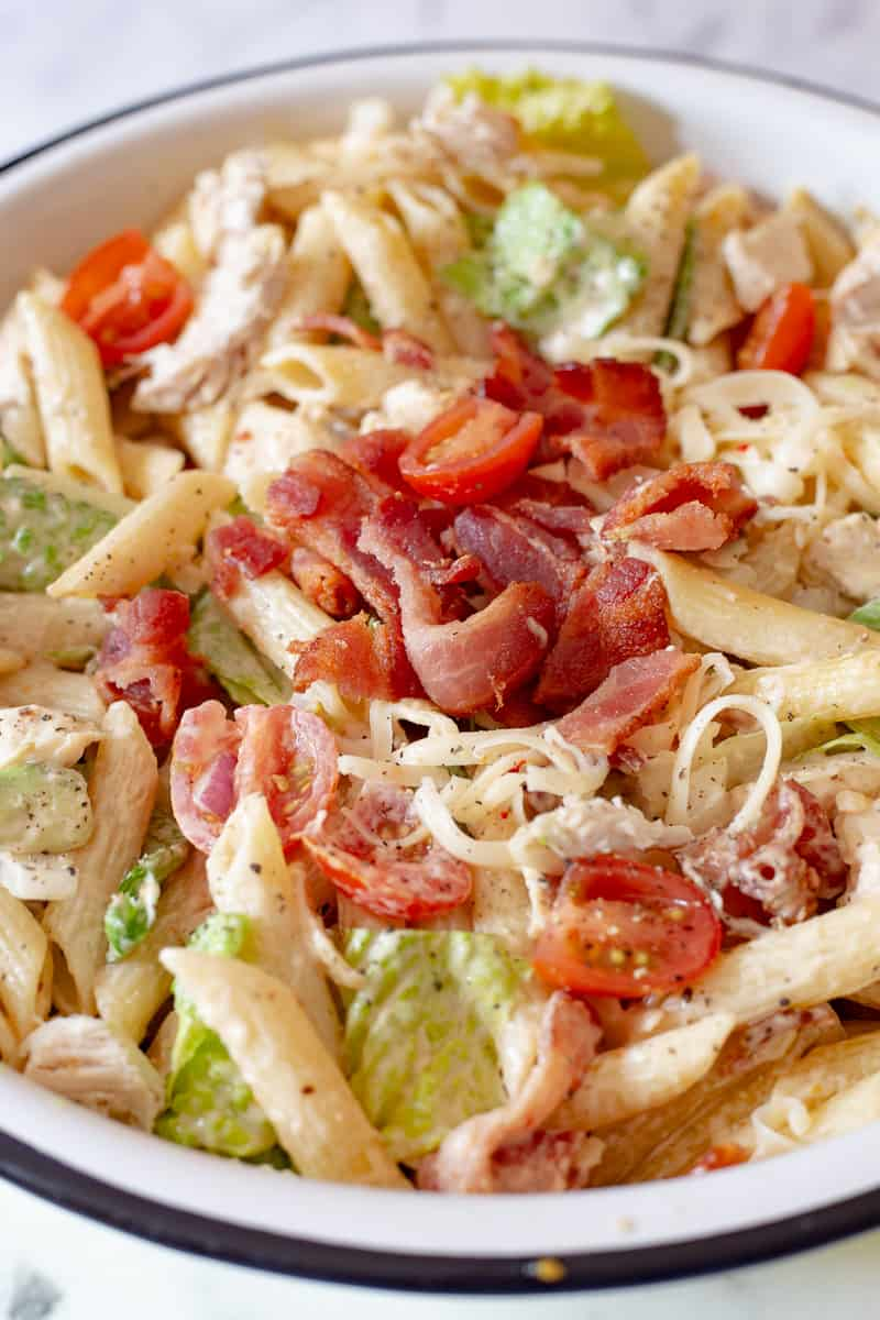 Close up image of BLT pasta salad with chicken in white bowl.