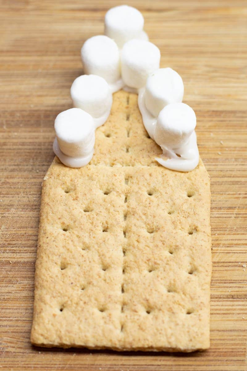 Marshmallows are added to the roof line on the gingerbread house.