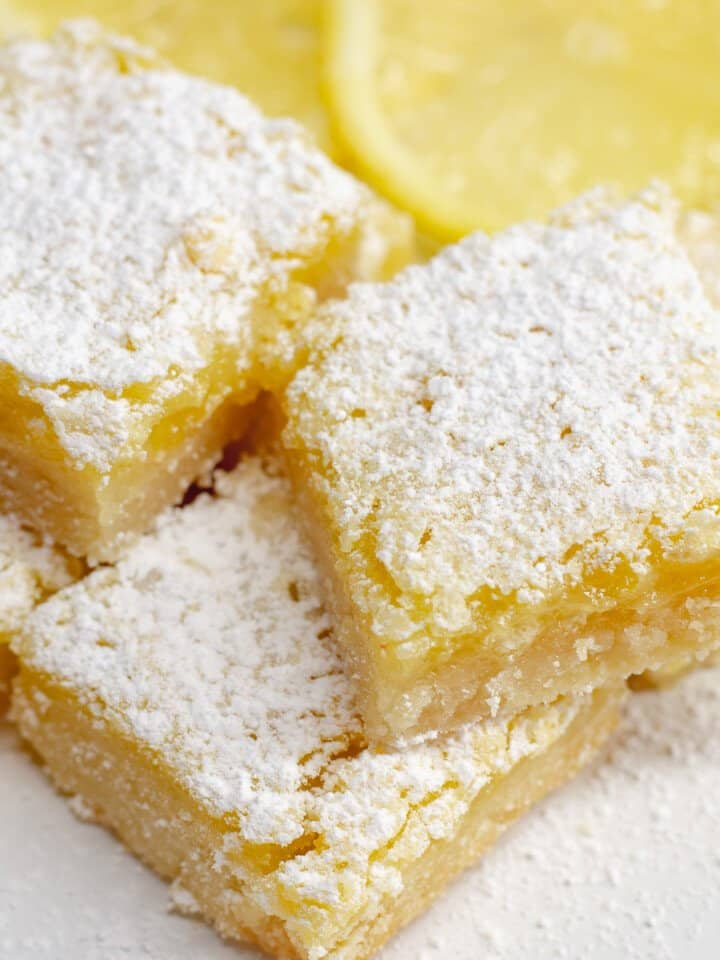 Close up image of lemon bars on white plate with lemon slices in background.