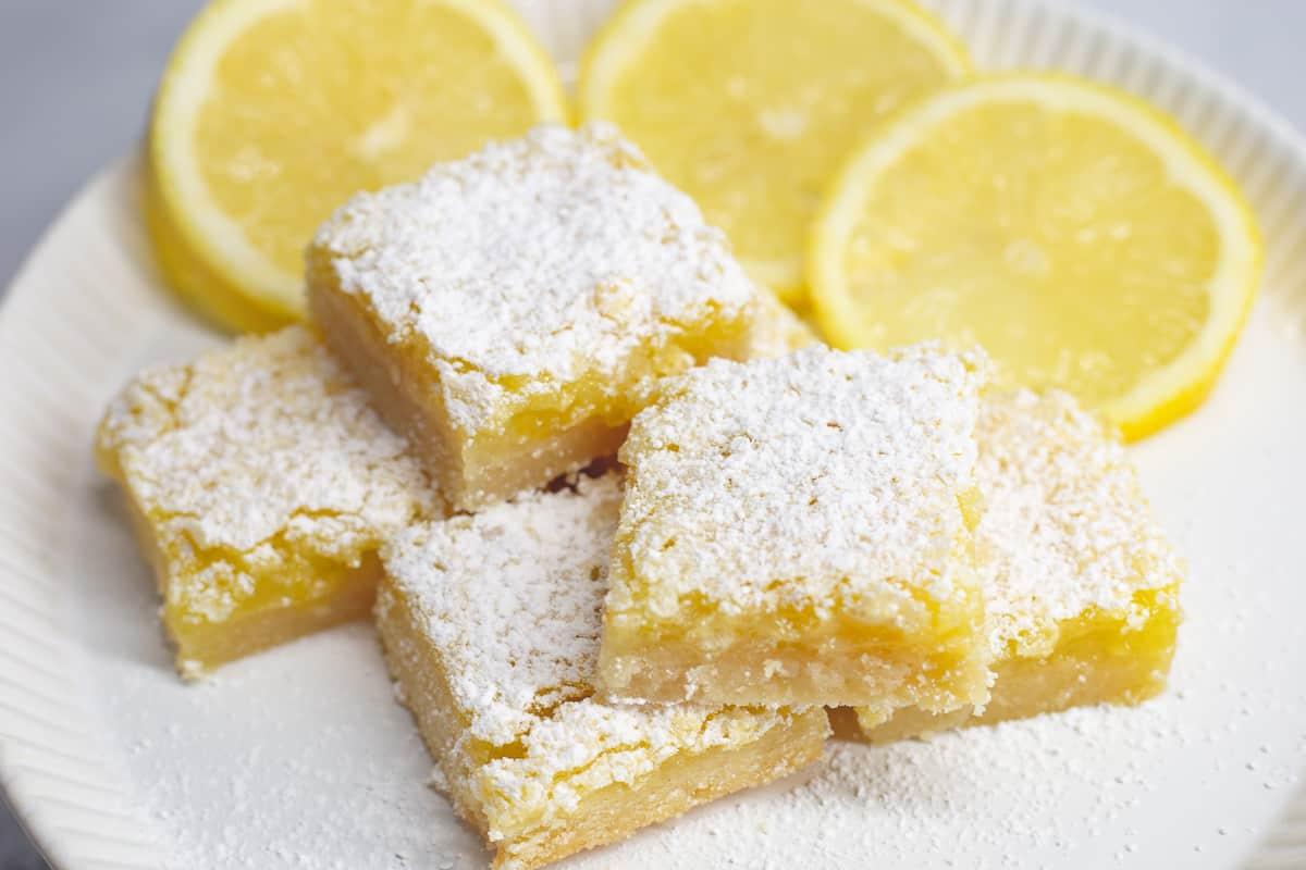 Best ever lemon bar recipe on a white plate with sliced lemons around the bars.