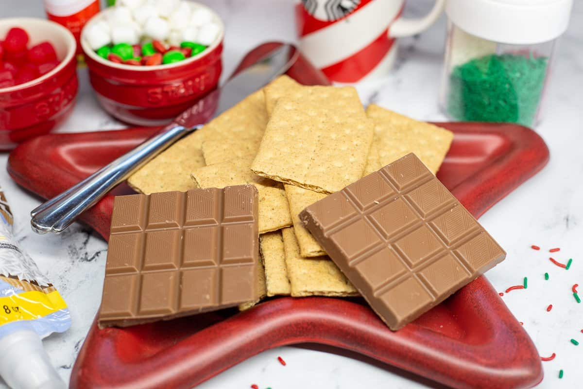 Graham cracker cookies and chocolate on red star-shaped plate with candies in the background.