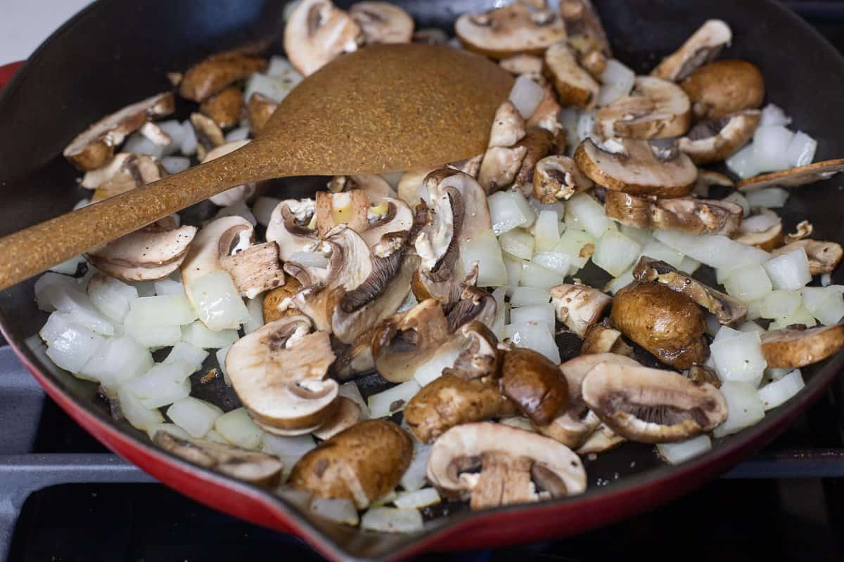 Onions, mushrooms and garlic in skillet with spoon.