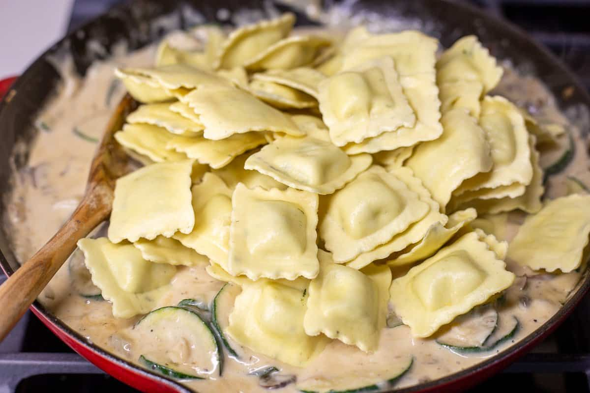Uncooked ravioli is added to the skillet.