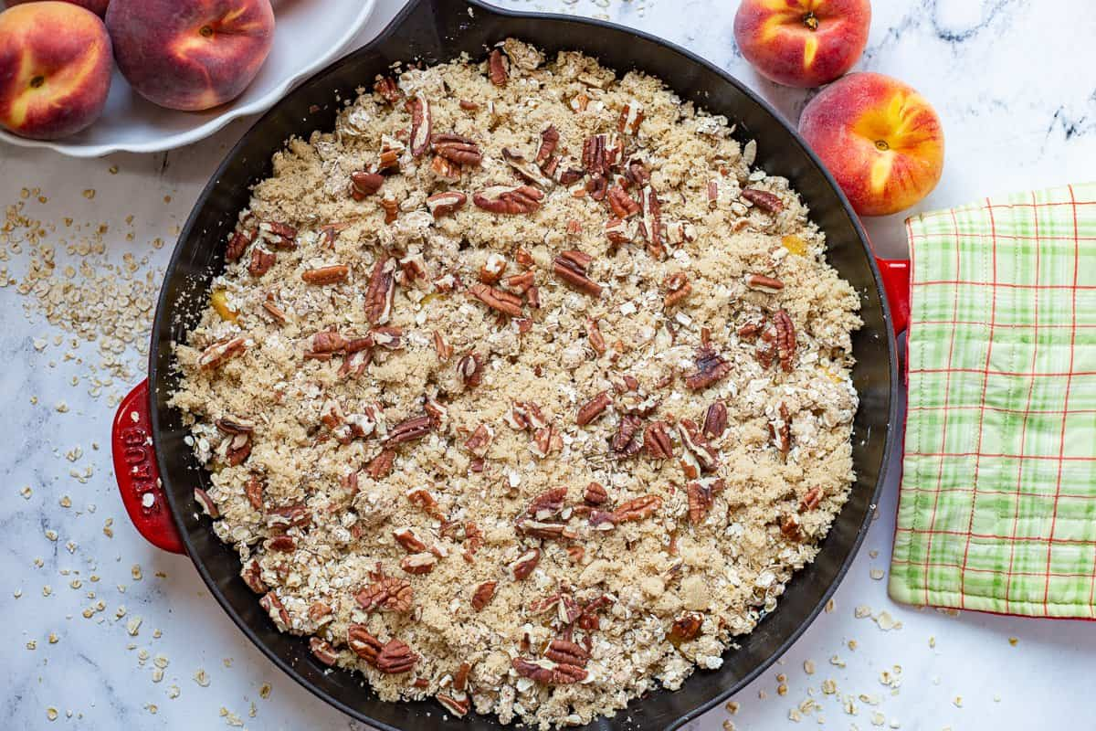 Brown sugar and pecans are sprinkled over the topping for peach crisp recipe.