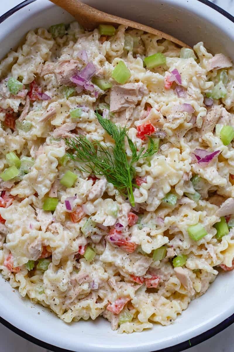 Close up image of tuna pasta salad in bowl with spoon.