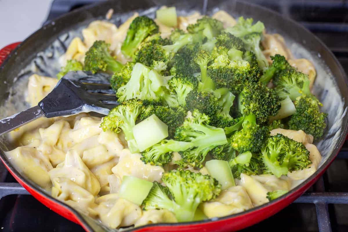 Broccoli is added to the tortellini and sauce in skillet.
