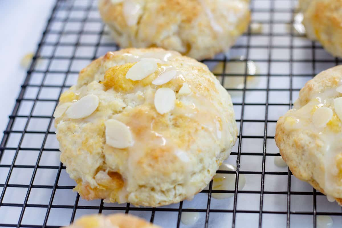 Scones on wire cooling rack are drizzled with glaze and almonds are scattered on top.
