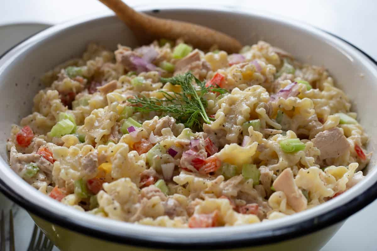 Chilled tuna pasta salad in bowl with serving spoon.