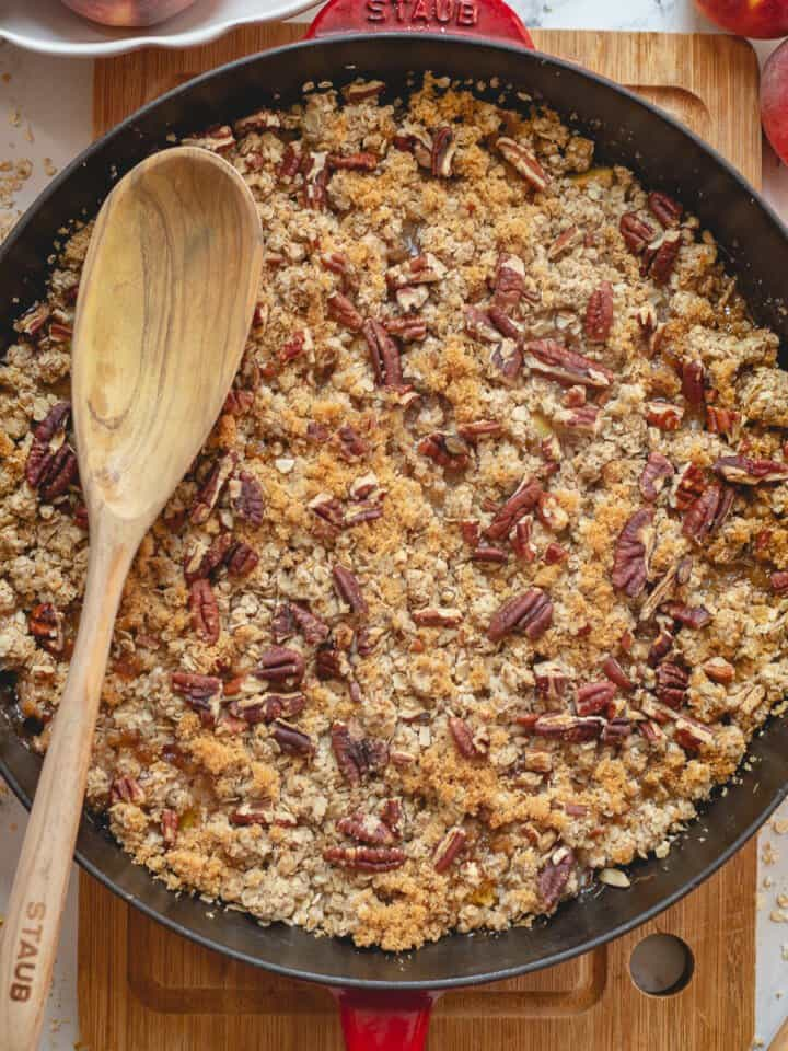 Close up image of baked peach crisp in cast iron skillet.